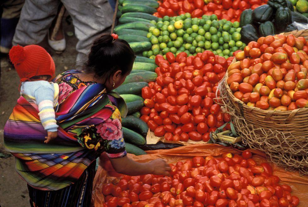 Una mujer compra verdura en un mercado en Guatemala.