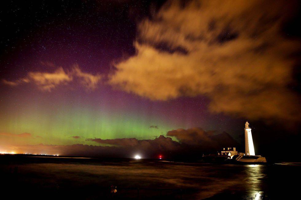 Las luces del norte brillan sobre el faro de Santa María en Northumberland, Inglaterra.