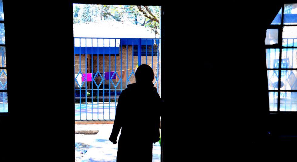 Una niña, en el umbral de una de las estancias del centro La Alianza, que ayuda a víctimas de trata a rehacer sus vidas.