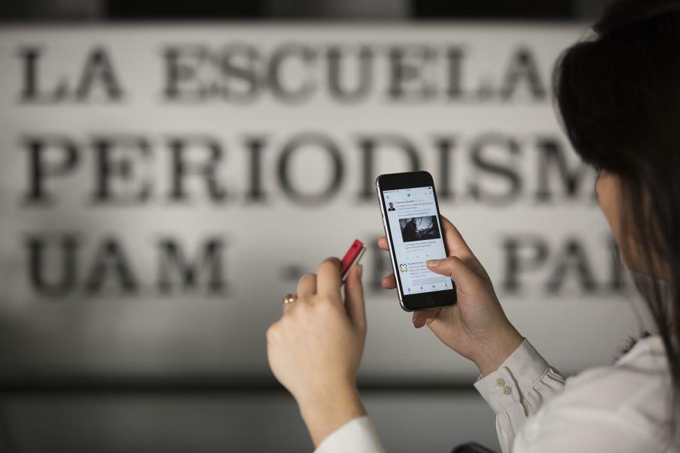 Una joven utiliza el móvil en las instalaciones de la Escuela de Periodismo.