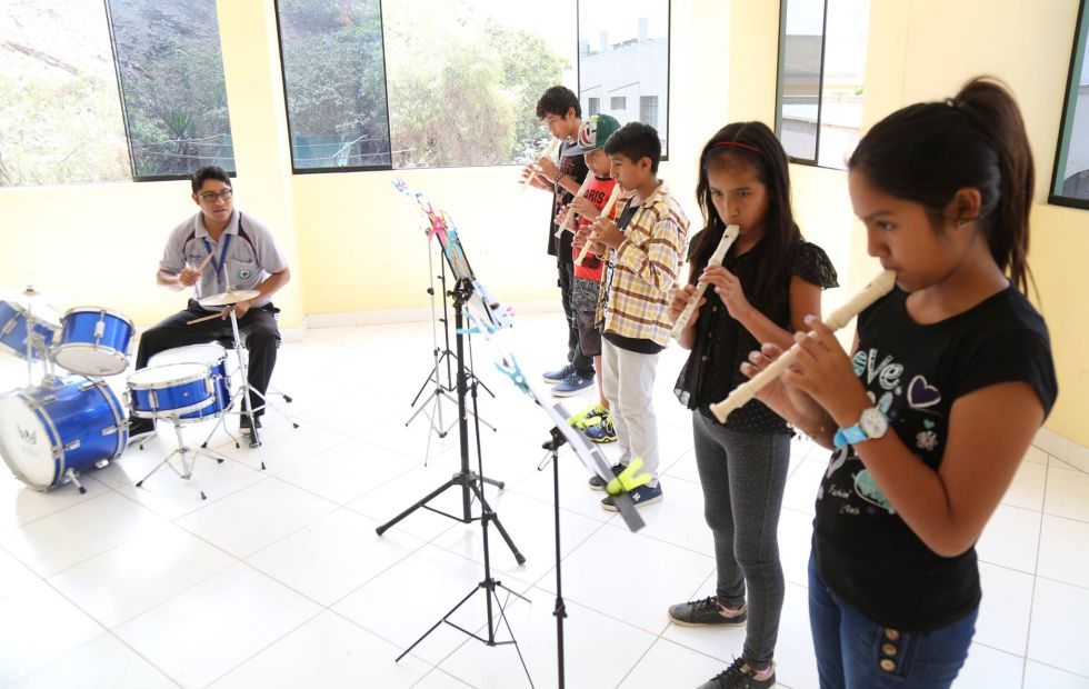 El profesor Espinoza dirige a los participantes de la escuela de música.