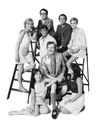 Michael Fish en el centro con falda y calcetines largos, junto a la actriz Susanna York, el cómico Peter Cook, el actor Tom Courtenay, el dramaturgo Joe Orton, las modelos Twiggy,Lucy Fleming y Miranda Chiu.
