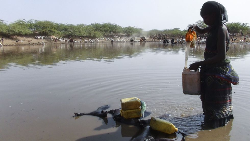 Una mujer etíope recoge agua de un estanque construido para mejorar la resiliencia frente a la sequía.
