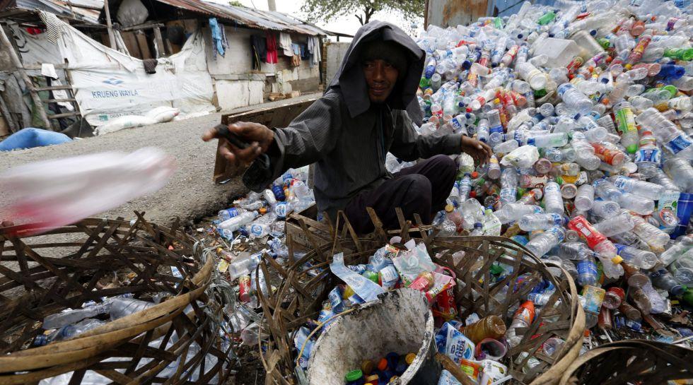 Un hombre recolecta botellas para reciclar en Indonesia.