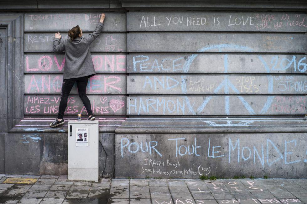 Una joven escribe, ayer, un mensaje en recuerdo de las víctimas de los atentados terroristas en un muro de la Plaza de la Bolsa de Bruselas.