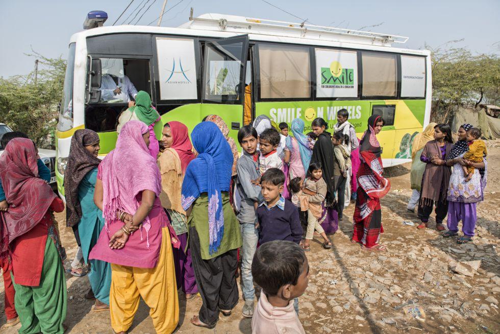 Pacientes se arremolinan en torno a un autobús de Smile on Wheels.