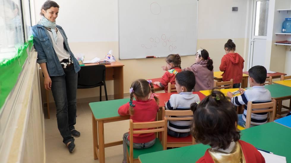 Joven voluntaria da apoyo pedagógico al equipo docente en el centro.