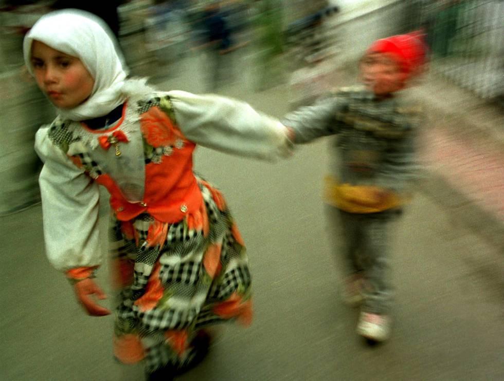 Una niña vestida con traje típico junto a su hermano en el zoco de Tánger (Marruecos)