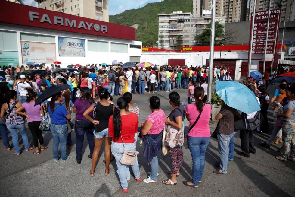 Grupo de personas haciendo cola para comprar papel higiénico y pañales en Caracas.