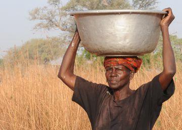 Una mujer carga con un bidón lleno de agua sobre su cabeza en Burkina Faso.