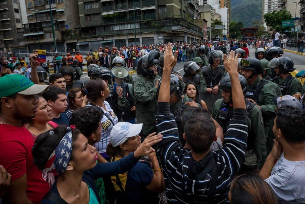 Un grupo de personas manifiestan contra miembros de la Guardia Nacional Bolivariana en Caracas en protesta por la carestía.