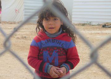 Una niña mira a cámara al otro lado de la verja del campo de refugiados de Zaatari, en Jordania.