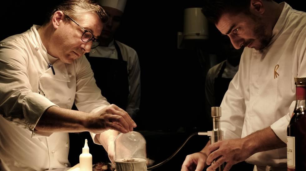 Joan Roca y, a la derecha, su hermano Jordi preparan un plato con madera.