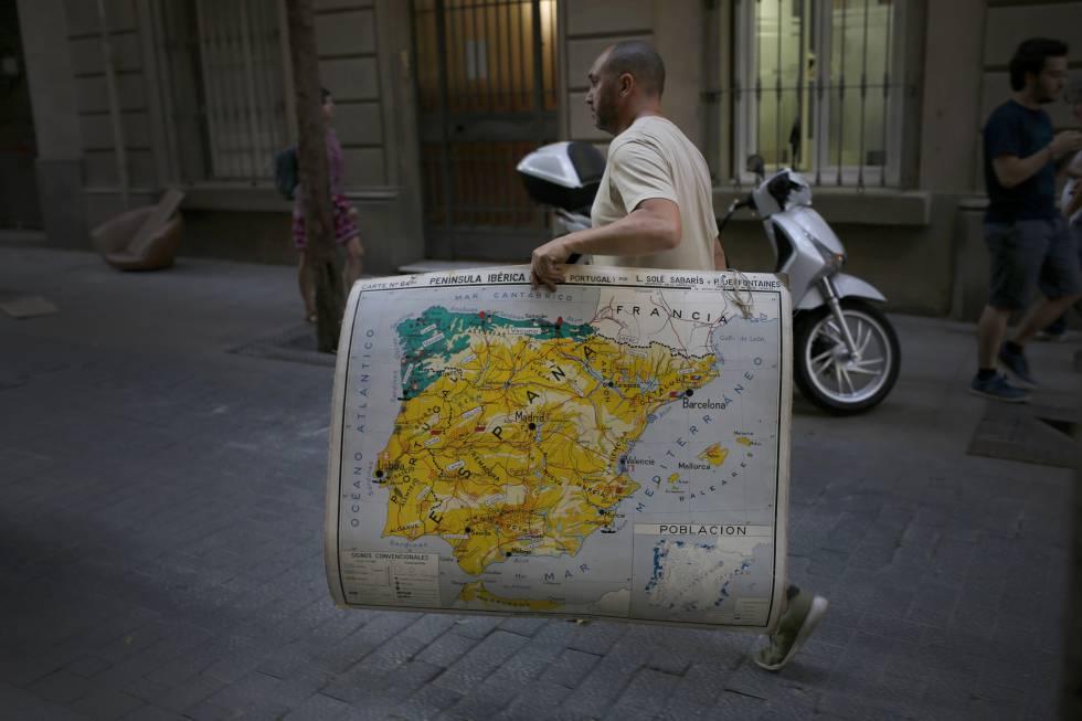 Un hombre lleva un mapa de España mientras camina por una calle en Barcelona