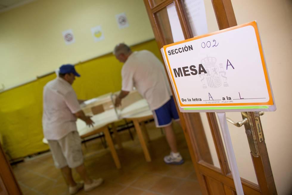 Dos operarios preparan las urnas y demás elementos en un colegio electoral el pasado día 26.