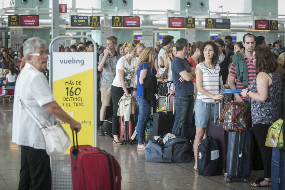 Passengers lining up at Vueling counters at Barcelona airport.