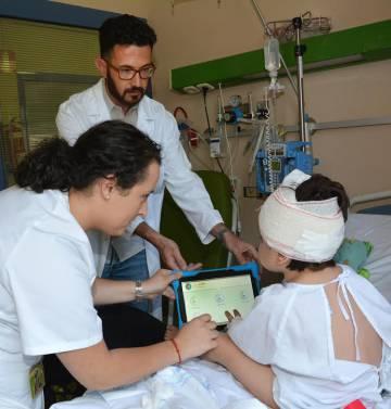 Un niño juega con PainAPPle para medir su grado de dolor postoperatorio.