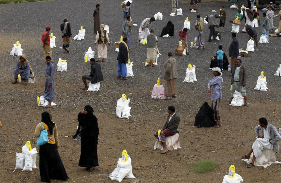 Ciudadanos yemeníes recogen bolsas con alimentos donados por un organismo local en Sanaía (Yemen).