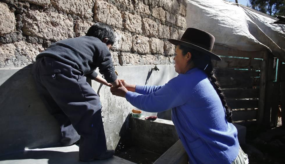 Marcelina ayuda a su hijo de seis años a lavarse las manos antes de almorzar.