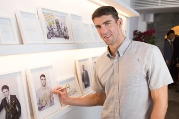 Phelps firma su foto en blanco y negro en el pequeño 'hall of fame' de OMEGA House en la villa olímpica de Río 2016.