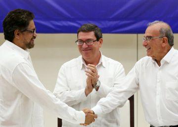 Los negociadores del Gobierno y las FARC se dan la mano tras el anuncio del acuerdo.