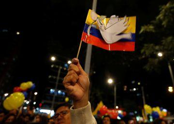 Un hombre alza una bandera Colombiana con la paloma de la paz tras el acuerdo de paz entre el gobierno colombiano y las FARC, en Bogotá.