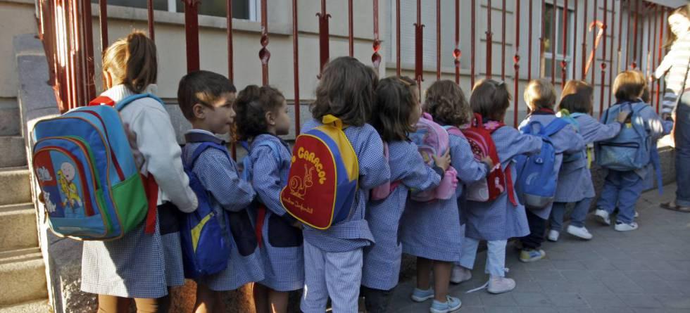 Niños haciendo cola a la puerta del colegio