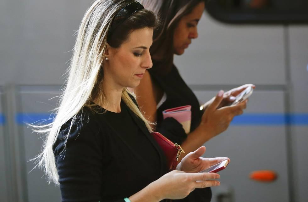 Dos mujeres usan el móvil  mientras pasean.
