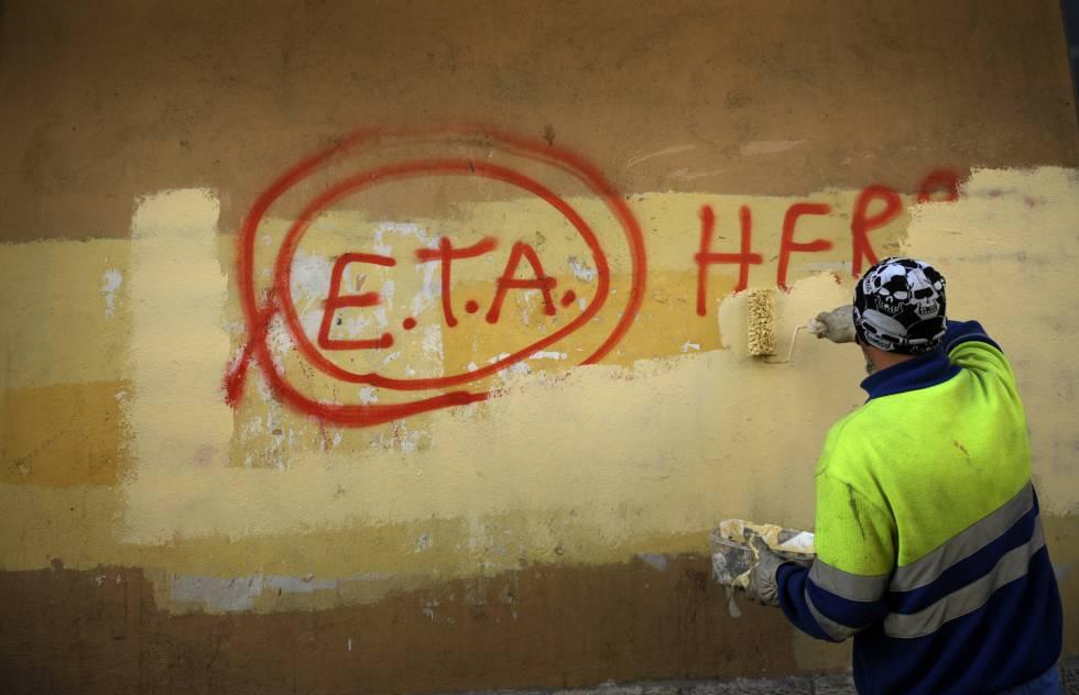 Un trabajador municipal borrando una pintada en la pared
