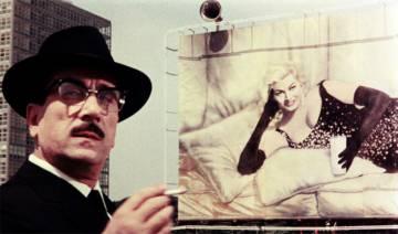 Anita Ekberg, al fondo, con un vaso de leche. En primer plano, Peppino De Filippo. La película es 'Bocaccio 70' (1962), de Federico Fellini.
