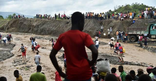 Haitianos cruzan el río La Digue en Petit Goave que se desbordó por las fuertes lluvias del huracán.