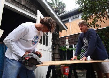 Dos personas protegen su casa con madera en Atlantic Beach, Florida.