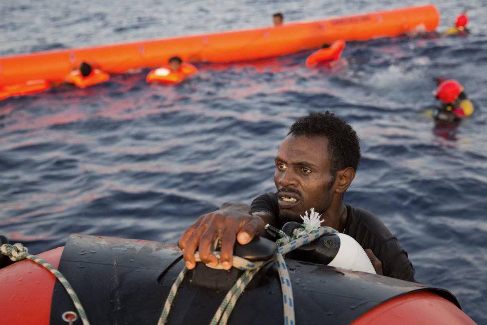Un migrante eritreo se agarra a un bote salvavidas después de haber saltado al agua desde una patera durante esta operación de rescate, a 13 kilómetros al norte de Sabratha (Libia).