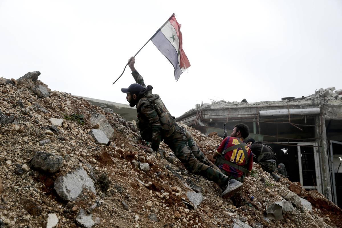 Un soldado sirio coloca una bandera nacional durante la batalla por el barrio de Ramusa.