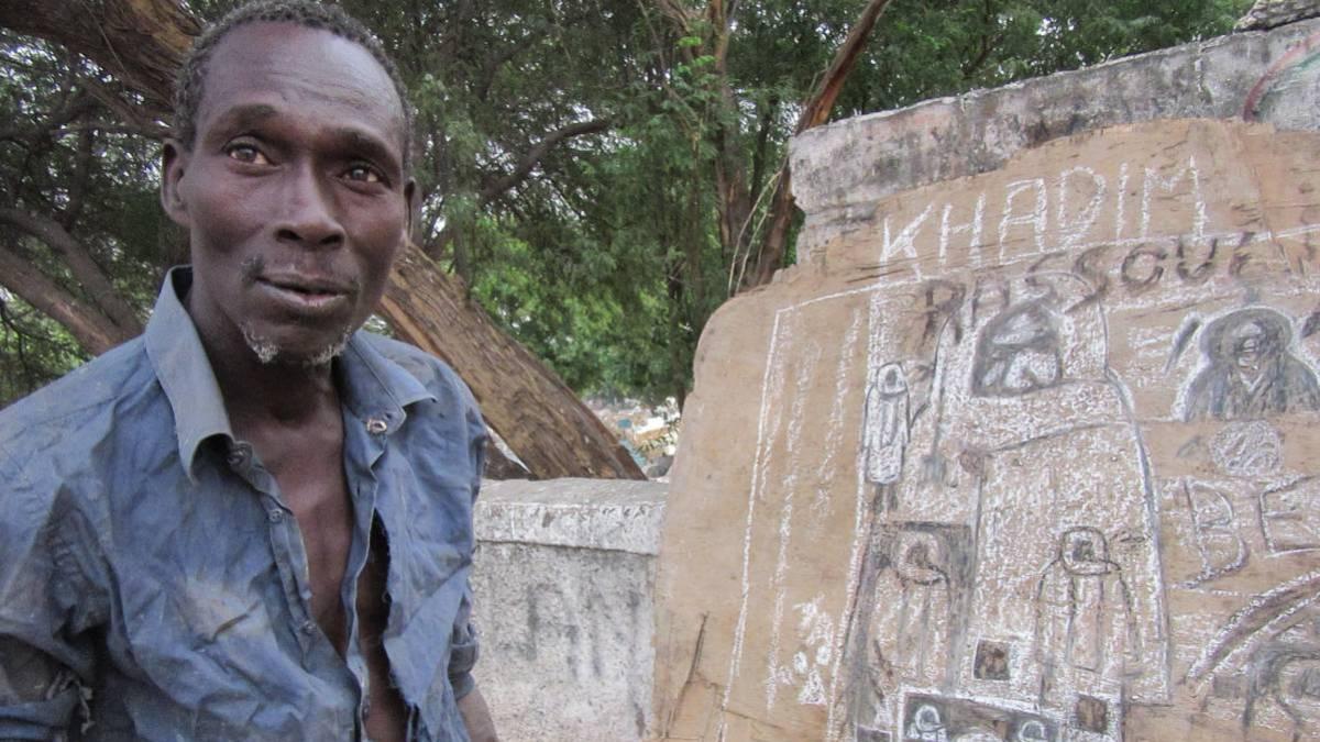 Pape Diop, junto a algunos de sus dibujos en el muro del cementerio de la Medina, en Dakar.