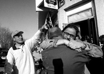 Dos hombres se abrazan en el exterior del bar de Balaguer, Lleida, dónde ha tocado la lotería.