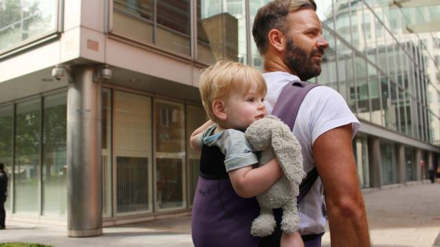 Un padre lleva a su hijo en una mochila portabebés.