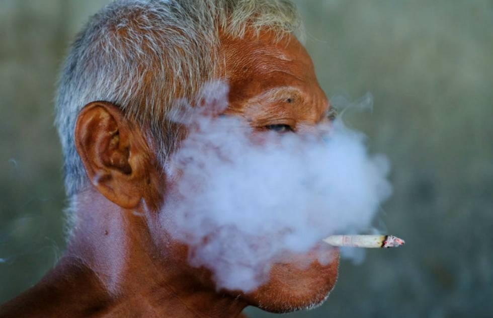 Un trabajador fuma un cigarrillo en una fábrica textil de Solo, en Indonesia.