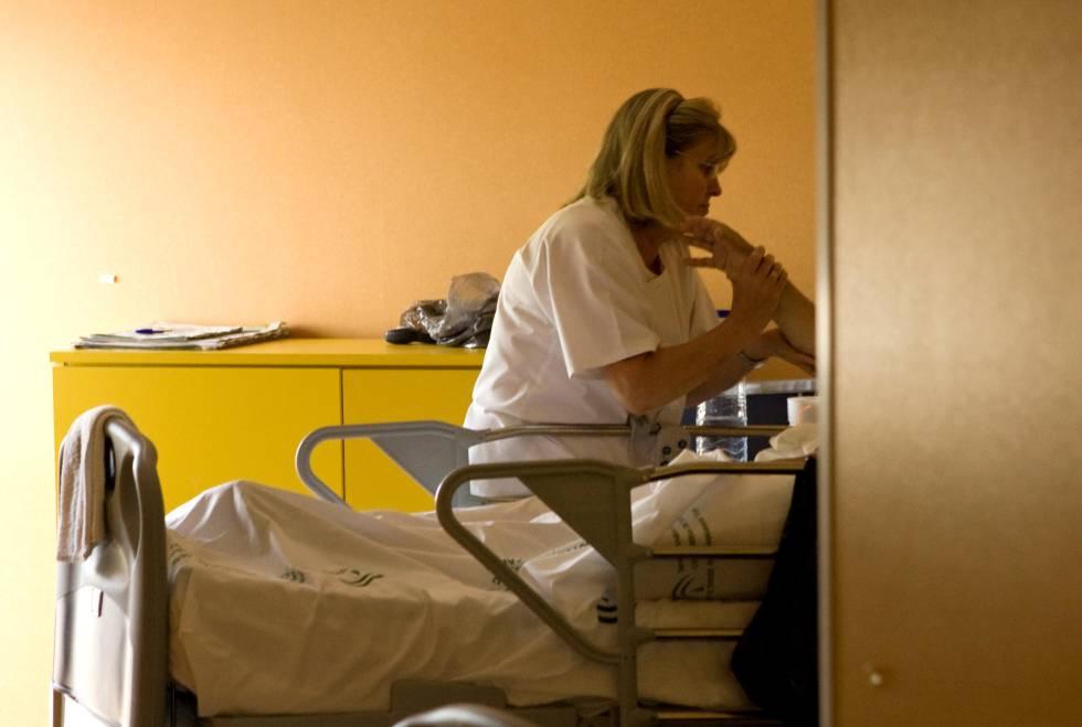 Un enfermo terminal recibe cuidados de una enfermera.