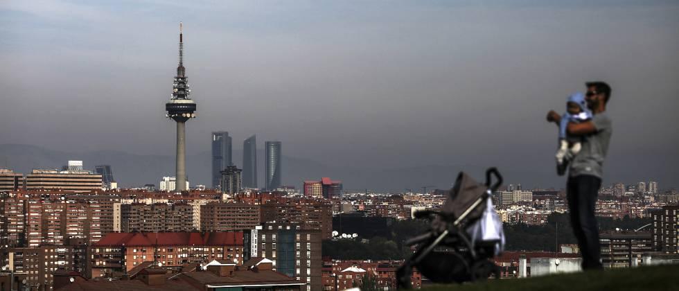 Un hombre con su bebé pasea por el barrio de Entrevías, en Madrid.