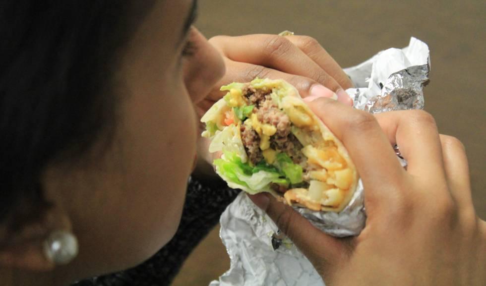 """Una persona comiendo un """"burgrito"""", una combinación de burrito mexicano y hamburguesa."""