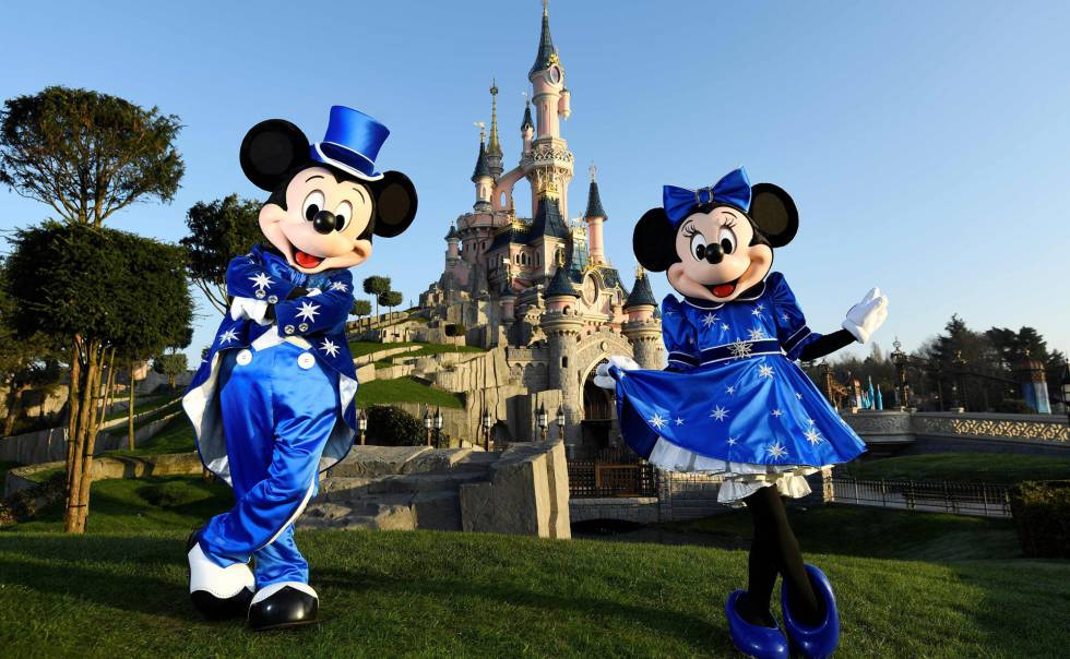 Mickey y Minnie posan frente al castillo.