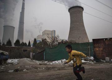 Un niño corre cerca de una central térmica de carbón en Pekín (China).