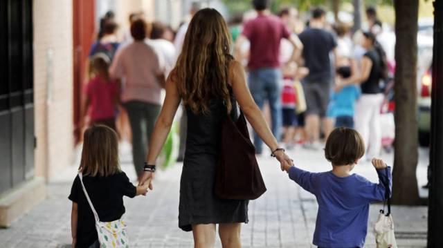 Una mujer lleva a sus hijos al colegio.