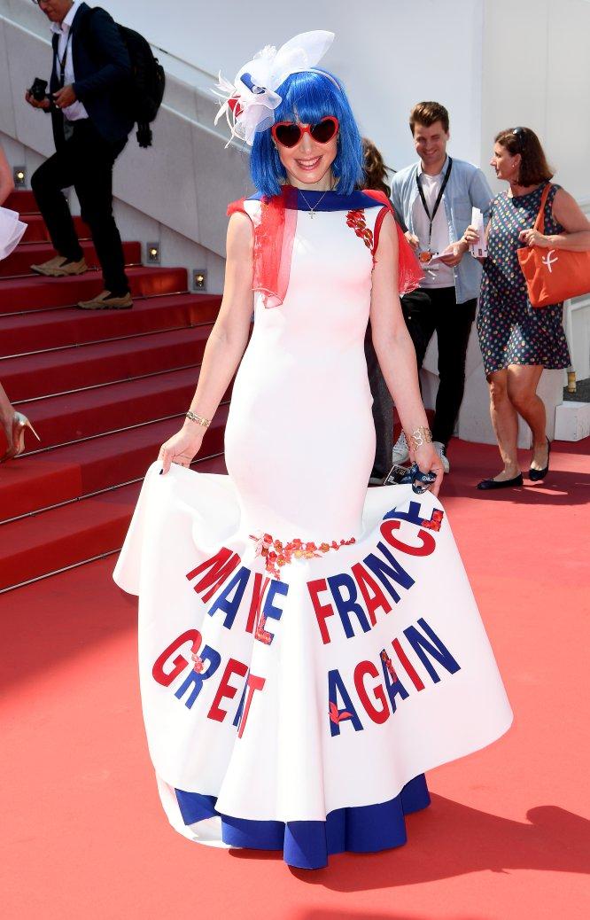 Una invitada posa en la alfombra roja con un vestido en el que se lee 'Make France Great Again' (Haz a Francia grande otra vez), uno de los lemas de Marine Le Pen, que la política francesa a su vez copió de Donald Trump.