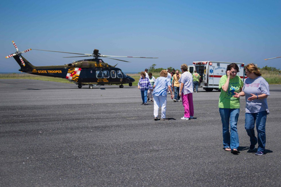 Sin hospital en la isla, las familias observan cómo una residente local es llevada en helicóptero debido a un dolor de pecho.