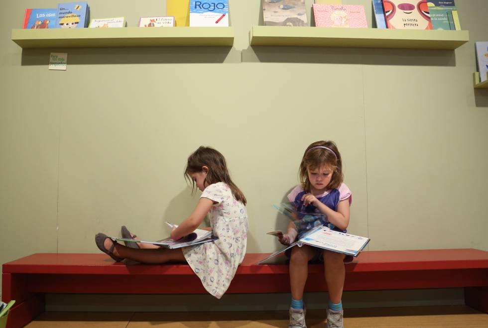 Feria del Libro de Madrid. Dos niñas miran libros en el pabellon infanti
