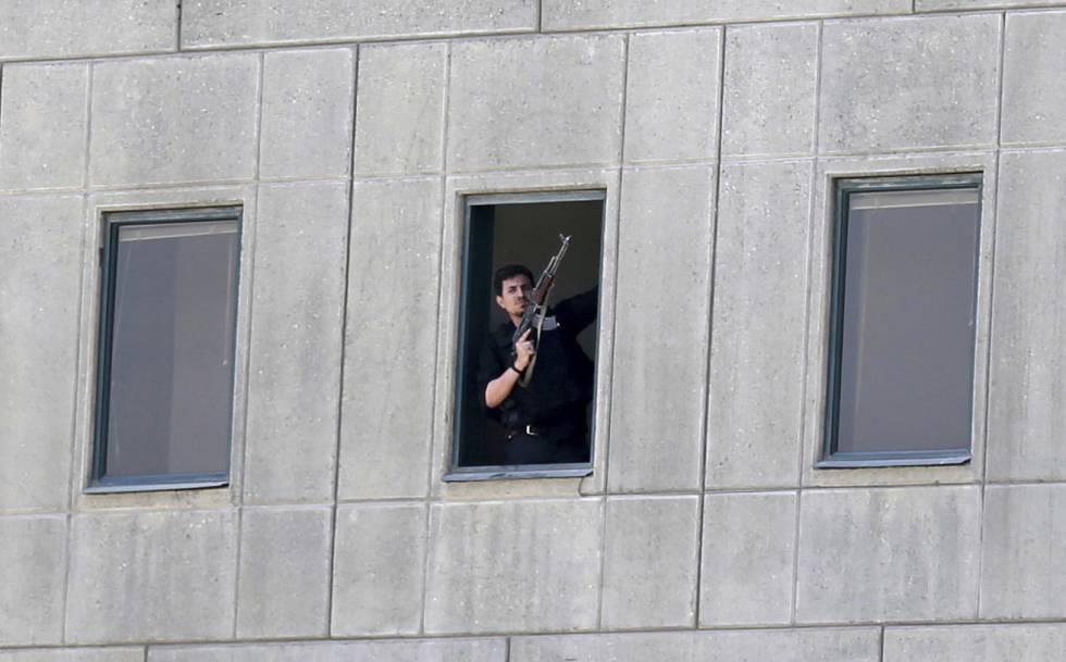 Un miembro de las fuerzas de seguridad se asoma a una ventana del Parlamento iraní en Teherán.