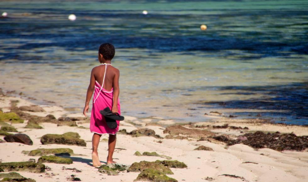 Una niña fiyiana camina por la orilla.