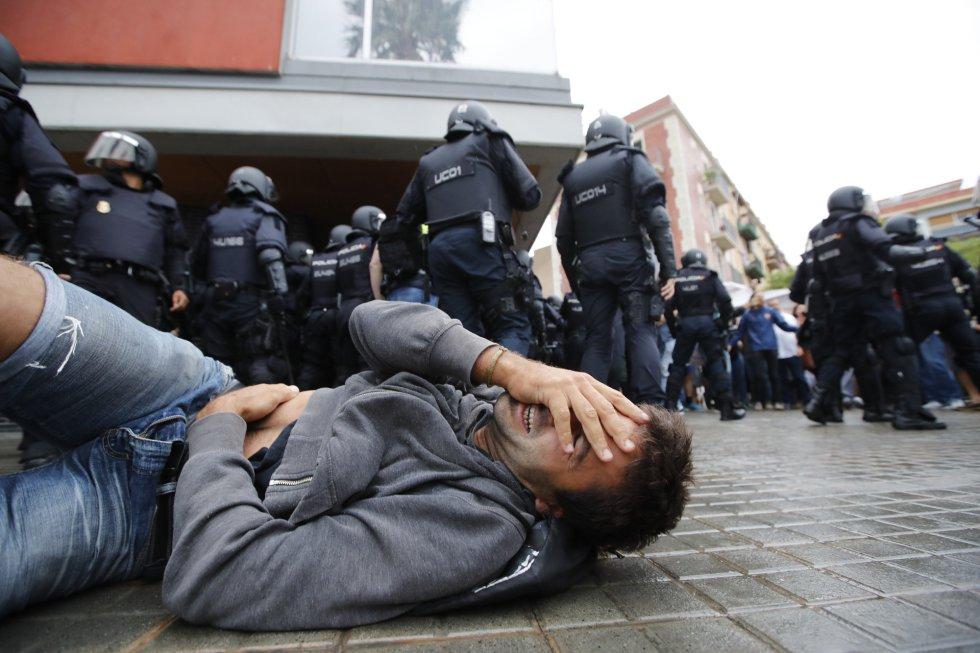 Un hombre cae al suelo durante la carga policial en la escola Mediterránea de la Barceloneta (Barcelona).